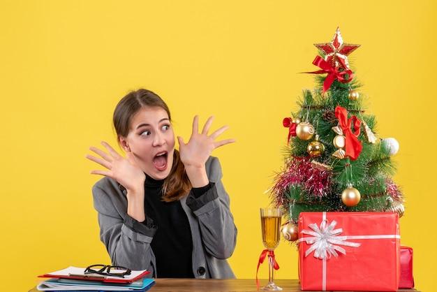 Vorderansicht überraschte süßes mädchen, das am schreibtisch mit geöffnetem handweihnachtsbaum und geschenkcocktail sitzt Kostenlose Fotos