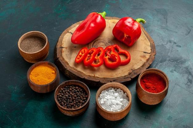 Vorderansicht verschiedene gewürze mit roter paprika auf dunkler oberfläche Kostenlose Fotos