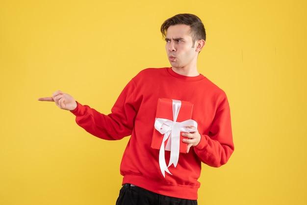 Vorderansicht verwirrte jungen mann mit rotem pullover, der etwas auf gelb zeigt Kostenlose Fotos