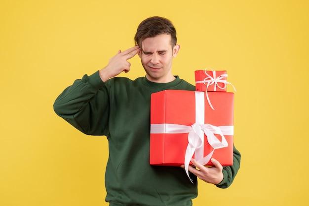 Vorderansicht verwirrte jungen mann mit weihnachtsgeschenk, das auf gelb steht Kostenlose Fotos