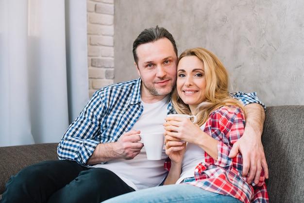Vorderansicht von den glücklichen jungen paaren, welche die kaffeetasse sitzt auf sofa hält Kostenlose Fotos