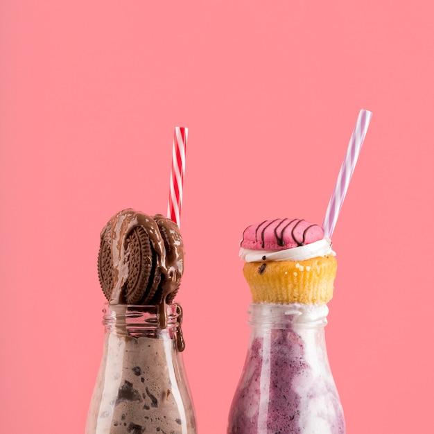 Vorderansicht von desserts mit keks und muffins mit strohhalmen Kostenlose Fotos