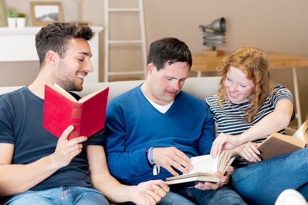 Vorderansicht von drei freunden, die auf sofa lesen Kostenlose Fotos
