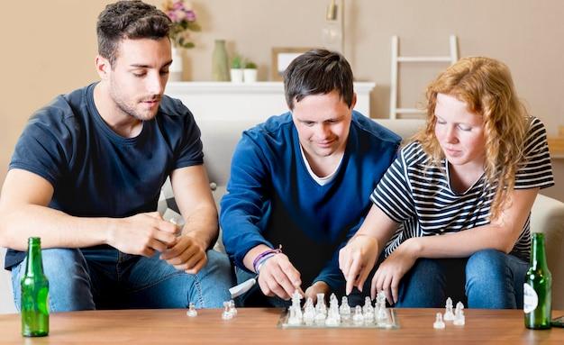 Vorderansicht von drei freunden, die schach spielen Kostenlose Fotos