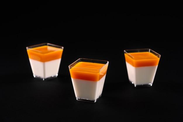 Vorderansicht von drei kleinen quadratischen gläsern mit milchiger panna cotta, die mit leuchtend orangefarbenem belag verziert sind. süßes köstliches dessert lokalisiert auf schwarzem studiohintergrund. lebensmittelkonzept. Premium Fotos