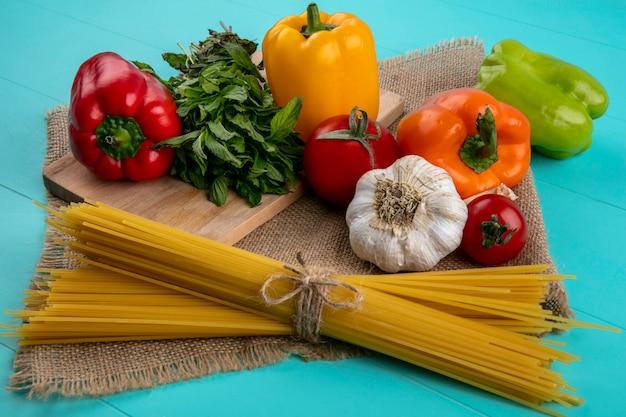 Vorderansicht von farbigen paprika auf einem schneidebrett mit rohen minzspaghetti und knoblauch auf einer türkisfarbenen oberfläche Kostenlose Fotos