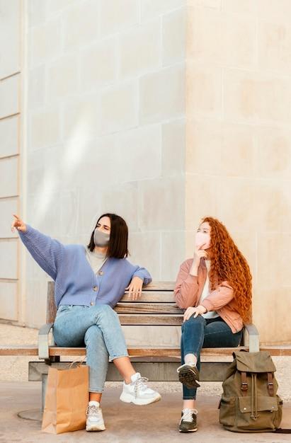 Vorderansicht von freundinnen mit gesichtsmasken draußen sitzen auf einer bank mit kopierraum Kostenlose Fotos