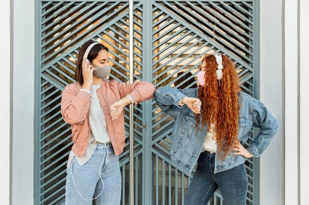 Vorderansicht von freundinnen mit gesichtsmasken im freien, die den ellbogengruß tun Kostenlose Fotos