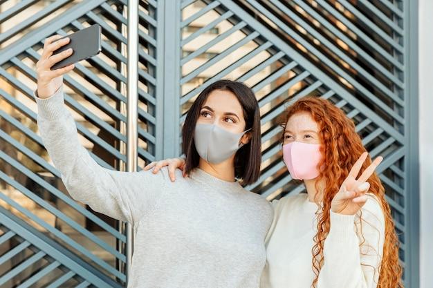 Vorderansicht von freundinnen mit gesichtsmasken im freien, die ein selfie nehmen Kostenlose Fotos