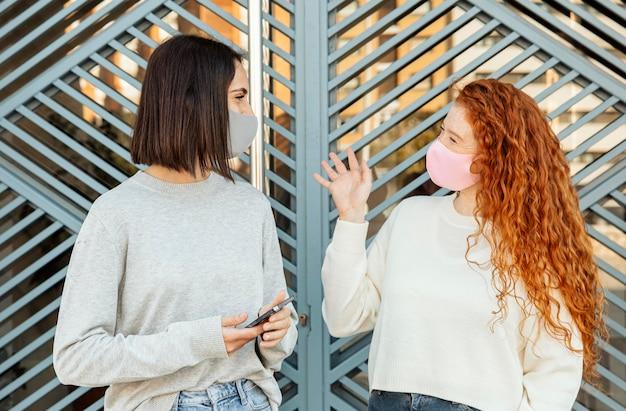 Vorderansicht von freundinnen mit gesichtsmasken im freien unterhalten Kostenlose Fotos