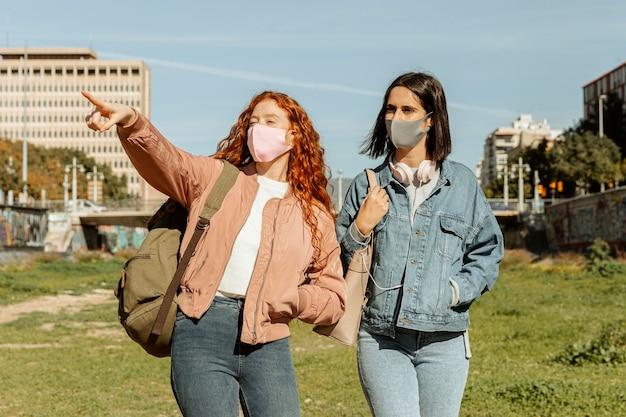 Vorderansicht von freundinnen mit gesichtsmasken im freien zusammen Kostenlose Fotos
