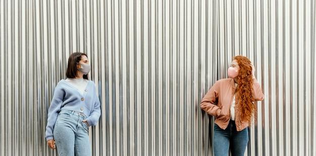 Vorderansicht von freundinnen mit gesichtsmasken im freien Kostenlose Fotos