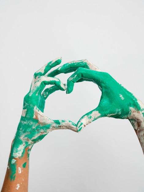 Vorderansicht von gemalten händen, die herz machen Kostenlose Fotos