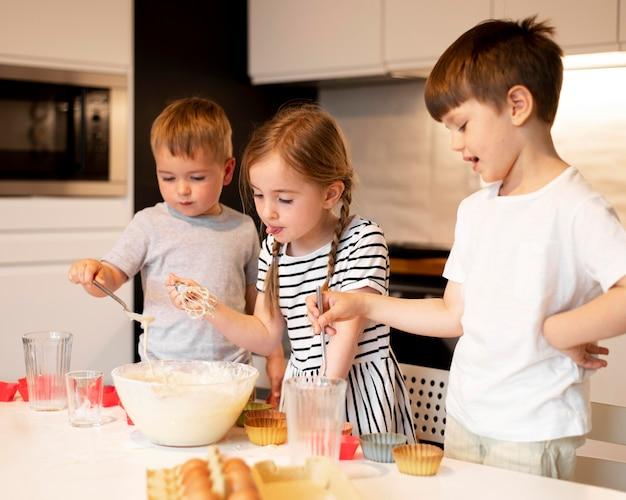 Vorderansicht von geschwistern, die zu hause kochen Kostenlose Fotos