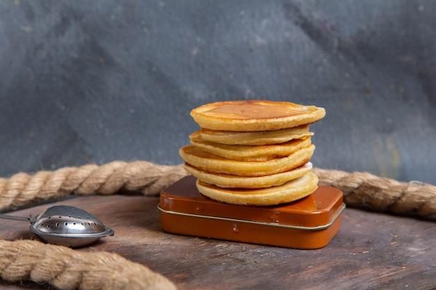 Vorderansicht von köstlichen leckeren muffins rund mit seilen auf der grauen oberfläche geformt Kostenlose Fotos