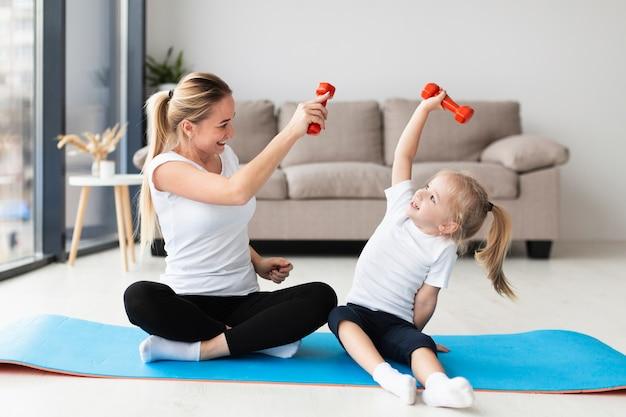 Vorderansicht von mutter und kind, die zu hause mit gewichten trainieren Premium Fotos