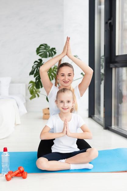 Vorderansicht von mutter und tochter in der yoga-haltung zu hause Premium Fotos