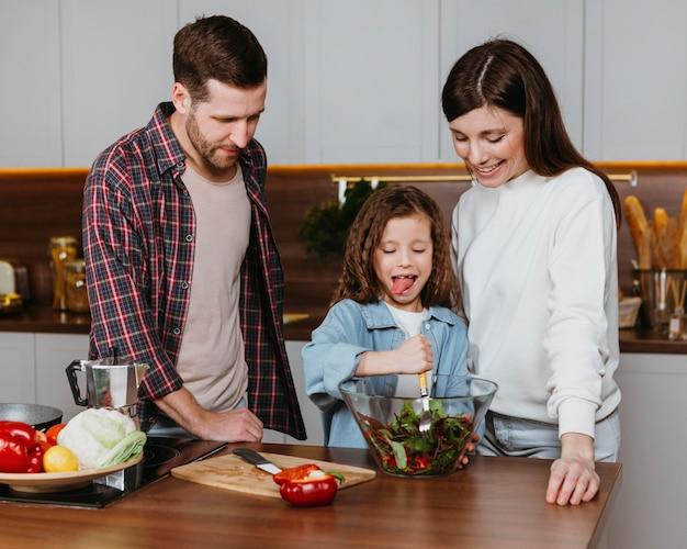 Vorderansicht von mutter und vater mit kind, das essen in der küche zubereitet Kostenlose Fotos