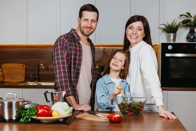 Vorderansicht von mutter und vater mit tochter, die in der küche aufwirft Kostenlose Fotos