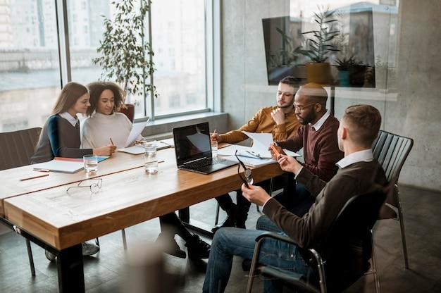 Vorderansicht von personen, die eine besprechung im büro haben Kostenlose Fotos
