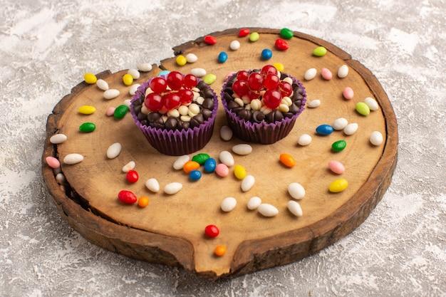 Vorderansicht von schokoladenbrownies mit bonbons auf dem holzbrett Kostenlose Fotos