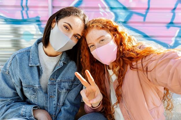 Vorderansicht von smiley-freundinnen mit gesichtsmasken im freien, die ein selfie nehmen Kostenlose Fotos