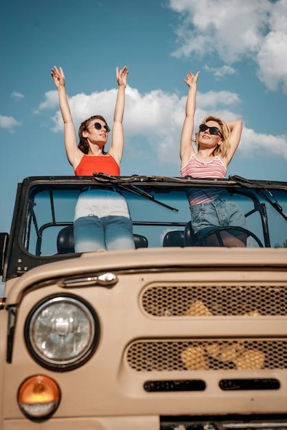 Vorderansicht von zwei frauen, die spaß beim reisen mit dem auto haben Kostenlose Fotos