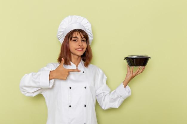 Vorderansicht weiblicher koch im weißen kochanzug, der schüssel auf hellgrüner oberfläche hält Kostenlose Fotos