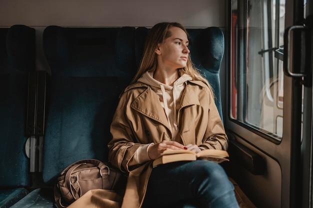 Vorderansicht weiblicher passagier, der in einem zug sitzt Kostenlose Fotos