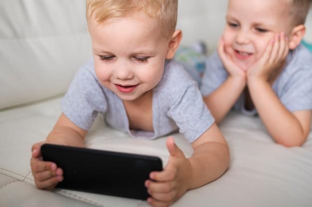 Vorderansichtbrüder, die auf smartphone spielen Kostenlose Fotos