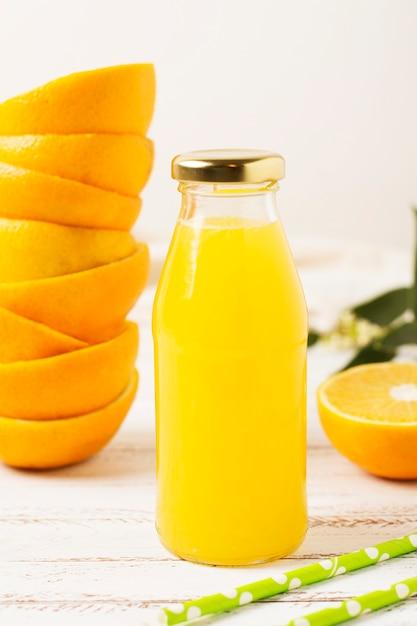 Vorderansichtflasche mit orangensaft Kostenlose Fotos