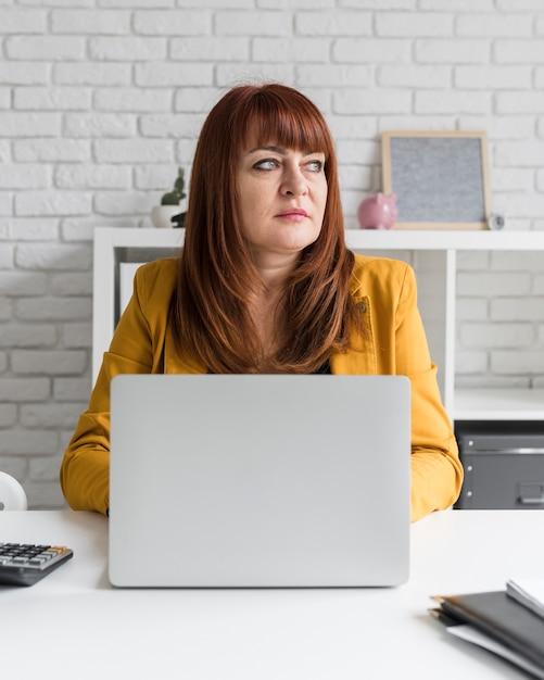 Vorderansichtfrau, die an laptop arbeitet Kostenlose Fotos