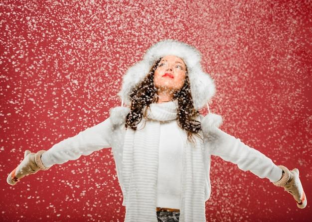 Vorderansichtfrau, die den schnee genießt Kostenlose Fotos