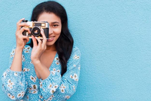 Vorderansichtfrau, die ein foto macht und kamera betrachtet Kostenlose Fotos