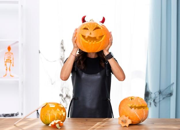 Vorderansichtfrau, die geschnitzten kürbis für halloween hält Kostenlose Fotos
