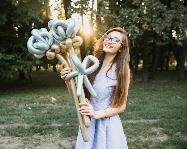 Vorderansichtfrau, die im sonnenlicht ballone hält Kostenlose Fotos