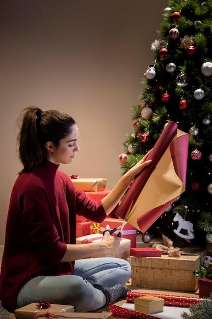 Vorderansichtfrau zu hause, die geschenke einwickelt Kostenlose Fotos