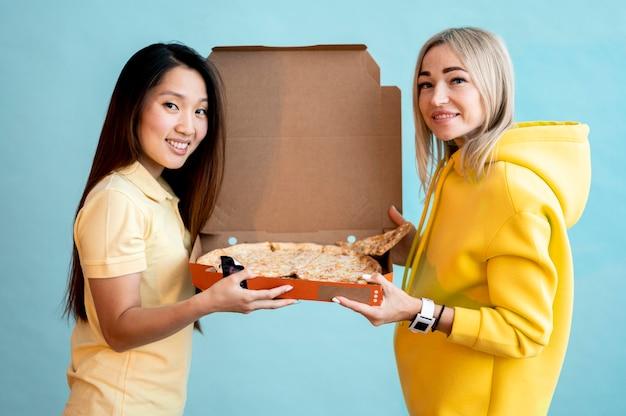 Vorderansichtfrauen, die eine schachtel mit pizza halten Kostenlose Fotos