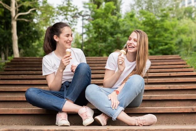 Vorderansichtfreunde, die auf treppe beim essen der eiscreme sitzen Kostenlose Fotos