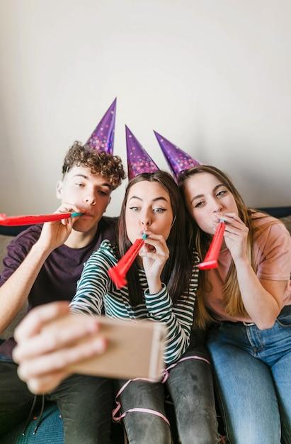 Vorderansichtfreunde, die hörner durchbrennen und ein selfie nehmen Kostenlose Fotos