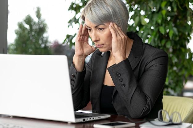 Vorderansichtgeschäftsfrau, die laptop betrachtet Kostenlose Fotos