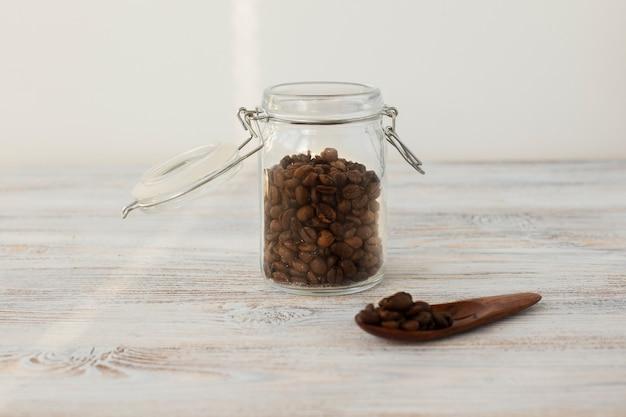 Vorderansichtglas gefüllt mit kaffeebohnen Kostenlose Fotos