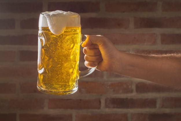Vorderansichthand, die halbes liter mit bier hält Kostenlose Fotos