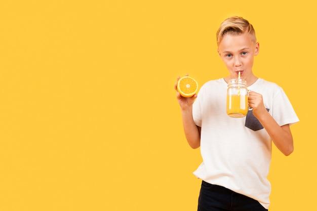 Vorderansichtjunge, der orangensaft trinkt Kostenlose Fotos