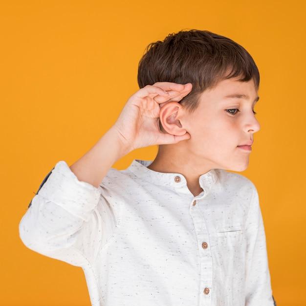 Vorderansichtjunge, der versucht, etwas zu hören Kostenlose Fotos