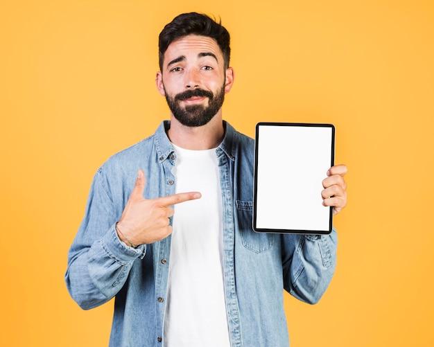 Vorderansichtkerl, der auf eine tablette zeigt Kostenlose Fotos