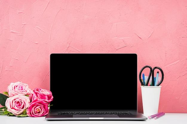 Vorderansichtlaptop mit blumenstrauß von rosen Kostenlose Fotos