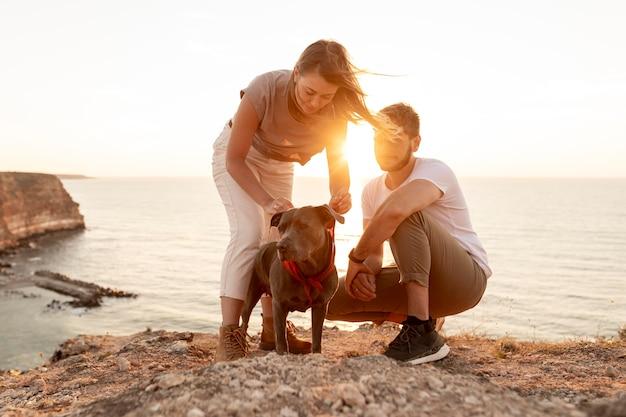 Vorderansichtleute, die mit ihrem hund bei sonnenuntergang spielen Premium Fotos
