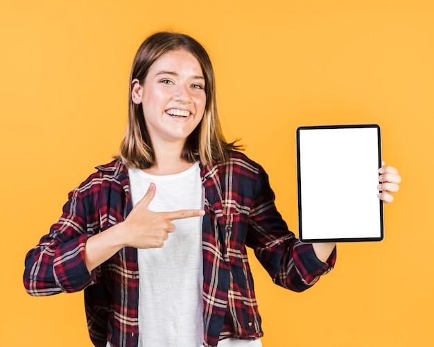 Vorderansichtmädchen, das auf eine tablette zeigt Kostenlose Fotos