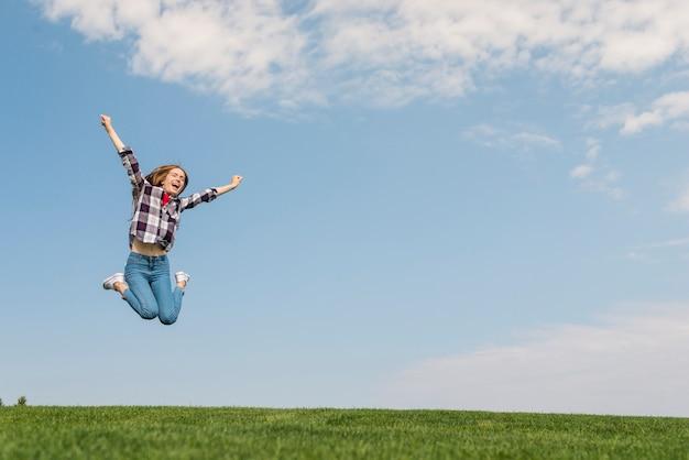 Vorderansichtmädchen, das so hoch springt, wie sie kann Kostenlose Fotos